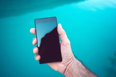 Using mobile phone by the swimming pool. Male hand holding smartphone with blank screen as copy space royalty free stock images