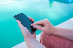 Using mobile phone by the swimming pool. Female hands holding smartphone royalty free stock photos