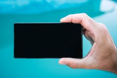 Using mobile phone by the swimming pool. Male hand holding smartphone with blank screen as copy space Stock Photography