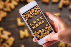 Using mobile phones to take photos of Cookies ABC in the form of word LOVE MAMA alphabet on old wood background, Valentines day Stock Photos