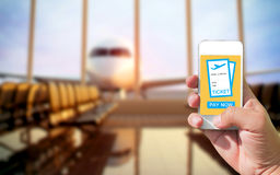 Using mobile smart phone buy ticket Airport Flight. Airplane bac. Kground bulr Stock Photo