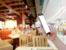 Using mobile smart phone with restaurant blur background,Vintage. Filter Stock Image