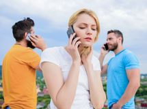 Using the mobile technology while on the move. Group of friends talk on cell phones. Modern people with smartphones stock image