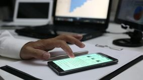 Using a mobile touch screen cell phone. In office stock footage