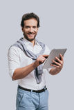 Using modern technologies. Beautiful young man in smart casual clothes working on digital tablet and looking at camera while standing against grey background Stock Photography