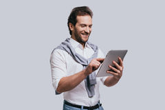 Using modern technologies. Beautiful young man in smart casual clothes working on digital tablet while standing against grey background Royalty Free Stock Photos