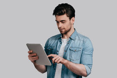 Using modern technologies. Good looking young man in blue jeans shirt working on digital tablet while standing against grey background Royalty Free Stock Image
