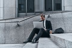 Using modern technologies. Good looking young man in full suit using laptop while sitting on the stairs outdoors Stock Photography