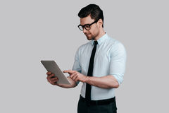 Using modern technologies. Good looking young man in white shirt and tie working on his digital tablet while standing against grey background Stock Images