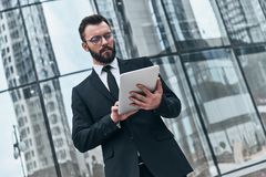 Using modern technologies. Good looking young man in full suit using digital tablet while standing outdoors Stock Image