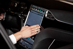 Using navigation system in car. Hand on display stock photography