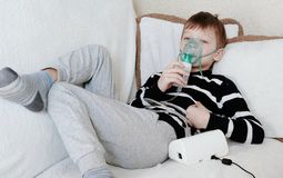 Using nebulizer and inhaler for the treatment. Boy inhaling through inhaler mask lying on the couch. stock photography