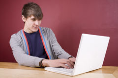 Using Notebook. Cool young man using a laptop in a home environment Royalty Free Stock Image