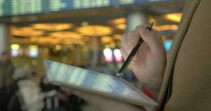 Using pad to send message before departure. Close-up shot of a woman typing on tablet PC with a pen at the airport. She sending a message standing by the flight stock video