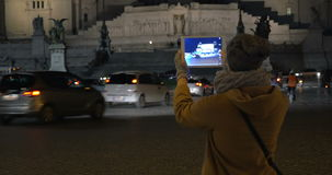 Using pad to shoot  Altar of Fatherland in Rome. Tilt shot of a woman coming up to the road and taking a picture of Altar of Fatherland at night. Female tourist stock video