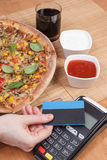 Using payment terminal with contactless credit card for paying in restaurant, finance concept, vegetarian pizza Stock Image