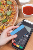 Using payment terminal with contactless credit card for paying in restaurant, finance concept, vegetarian pizza Stock Images