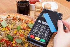 Using payment terminal with contactless credit card for paying in restaurant, finance concept, vegetarian pizza Royalty Free Stock Photo