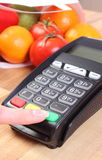 Using payment terminal, fruits and vegetables, cashless paying for shopping, enter personal identification number. Using payment terminal, enter personal Royalty Free Stock Images