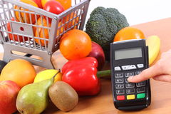 Using payment terminal, fruits and vegetables, cashless paying for shopping, enter personal identification number Royalty Free Stock Image