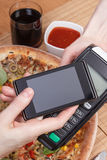 Using payment terminal and mobile phone with NFC technology for paying in restaurant, vegetarian pizza Stock Image
