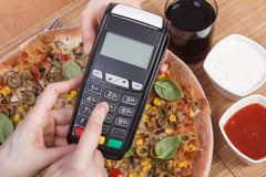 Using payment terminal for paying in restaurant, enter personal identification number, vegetarian pizza Royalty Free Stock Images