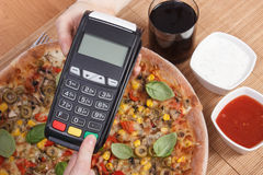 Using payment terminal for paying in restaurant, enter personal identification number, vegetarian pizza Stock Photo