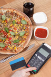 Using payment terminal for paying in restaurant, enter personal identification number, vegetarian pizza Royalty Free Stock Photography