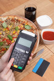 Using payment terminal for paying in restaurant, enter personal identification number, vegetarian pizza Stock Photos