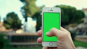 Using Phone App in Park on Background of Fountain. Man Using Phone App in the Park on the Background of the Fountain at Sunny Day stock footage