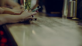 Using phone in the bar. Close up view of hands using a phone at a bar counter stock video