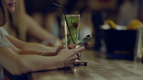Using phone in the bar. Young serious woman sitting in a bar using a phone with happy couple on background stock footage