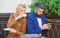 Using phone while date. Morning coffee. woman and man with beard relax in cafe. Couple in love on romantic date. Brutal. Using phone while date. Morning coffee stock photo