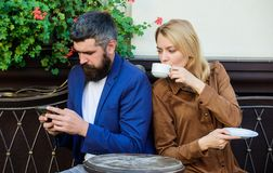 Using phone while date. Morning coffee. woman and man with beard relax in cafe. Couple in love on romantic date. Brutal. Using phone while date. Morning coffee royalty free stock photography