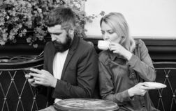 Using phone while date. Morning coffee. woman and man with beard relax in cafe. Couple in love on romantic date. Brutal. Using phone while date. Morning coffee royalty free stock images