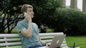 Using phone and laptop. Young man using phone and laptop sitting on a bench outdoor stock footage
