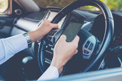Using phone sending a text while driving to work Royalty Free Stock Images