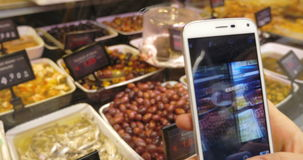 Using phone to make shots of olives and seafood. Close-up shot of customer using smartphone to take pictures of olives and seafood presented in the store stock video footage