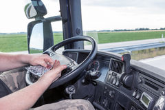 Using the pills while driving the truck. The driver is using the piil while driving the truck. The view from inside the truck cab Royalty Free Stock Photo