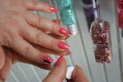 Using pink glitter nail polish. Lacquering. Nail polish using. She using a glitter pink nail polish Royalty Free Stock Photos