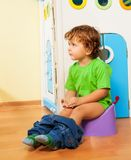 Using a potty. Two years old boy sitting on a potty with his pants off Stock Image
