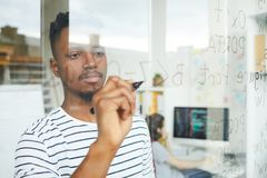 Using programming language for coding. Serious concentrated handsome young African-American web developer using programming language for coding and writing it on stock photo