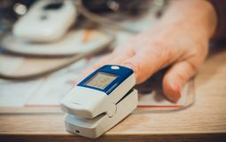 Using pulse oximeter on the hand for measuring pulse closeup royalty free stock images