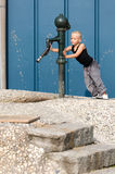 Using the pump. Little boy is using the waterpump Stock Image