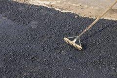 Using a rake to level asphalt pavement Stock Photo