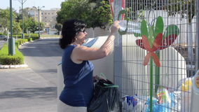 Using recycling container for plastic bottles. Woman throws away used plastic bottles into recycling container in the street stock footage