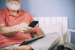 Using remote control. Senior man holding remote control in his hand to switch channels, digital tablet on his lap royalty free stock images