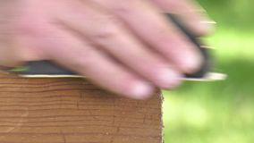 Using a sanding block on the edge of a board stock footage
