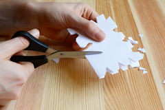 Using scissors to cut out a paper snowflake shape. Closeup of hands using scissors to cut out a paper snowflake shape Royalty Free Stock Photo