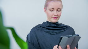 Using the smart pad an tile the hair colour sets. Slow motion RAW footage of a women seating at a hair dresser and looking  on the smart pad in her hands stock footage